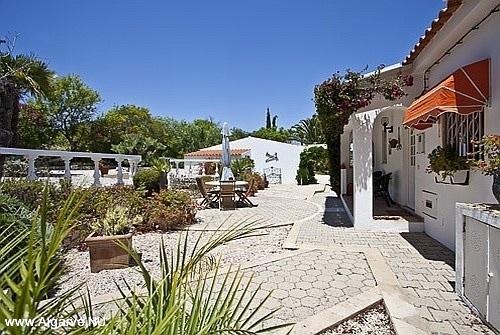 De achterkant van Vila Maria met een terras en tuin.