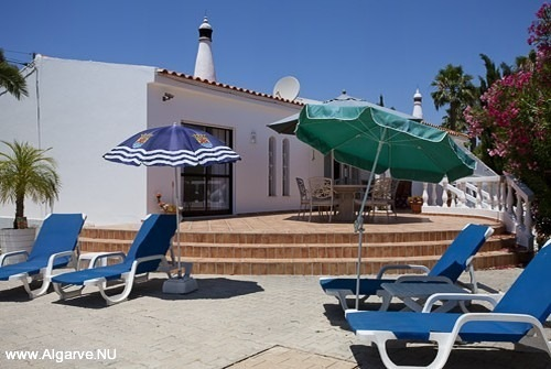 Het terras met parasols, stoelen en ligstoelen.