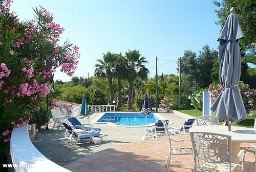 Het terras met parasol en ligstoelen en het zwembad op de achtergrond.