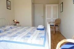 In de tweede slaapkamer staan twee éénpersoonsbedden naast elkaar.